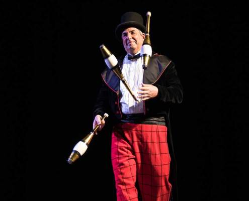 photo of a juggler performing with three clubs on stage