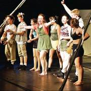 artist in residence performers standing on stage waving to their audience