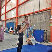 young child on a trapeze with the help of a NECCA coach