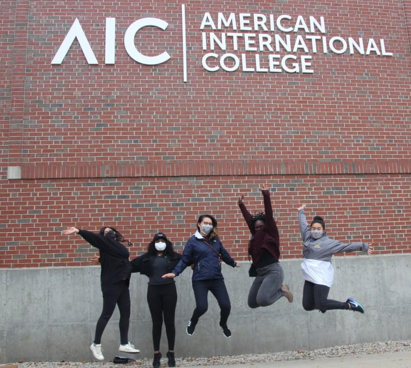 girls jumping under AIC sign