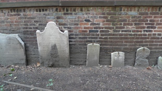 Row of headstones and footstones against the old (East) back wall.