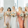 five women wearing wedding attire and holding wedding bouquets