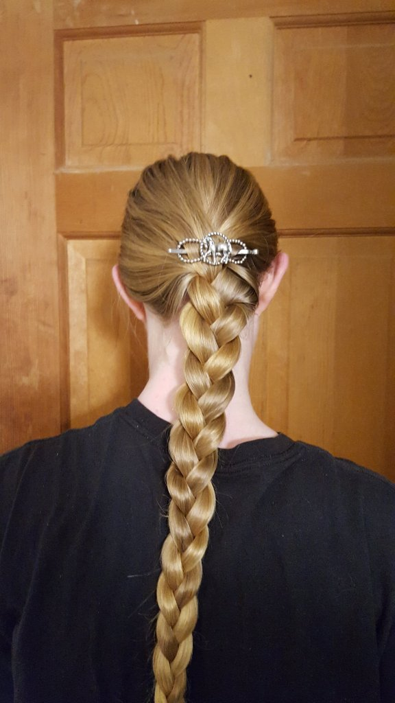 back of woman's head with long blonde hair braided and a Lilla Rose horse flexi clip above braid