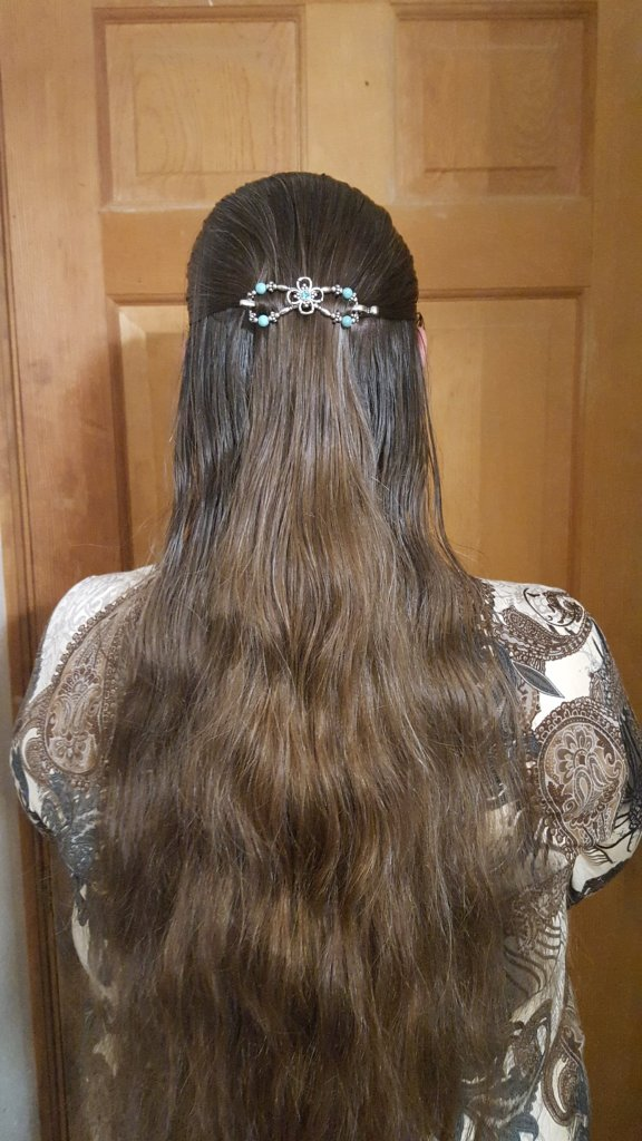 woman with very long brown hair wearing teal figure eight hair clip
