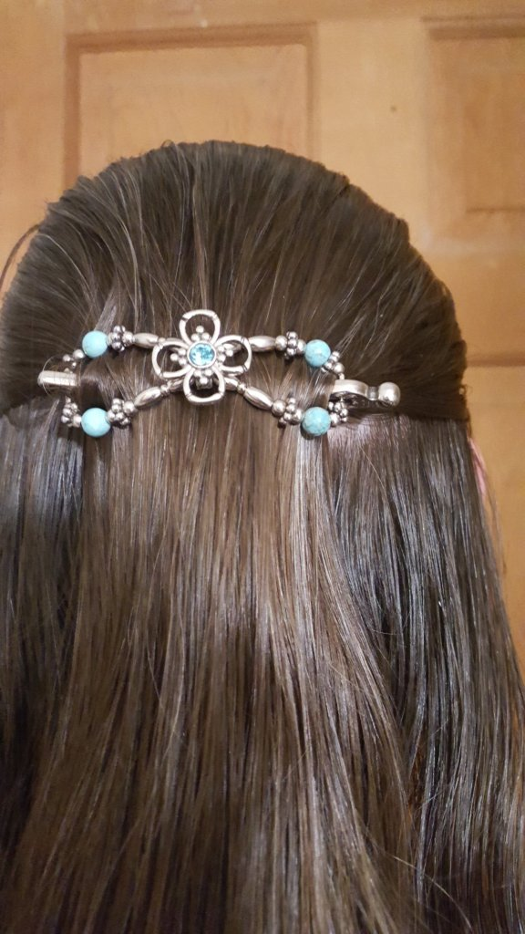 light teal stones on silver figure eight hair clip in woman's brown hair