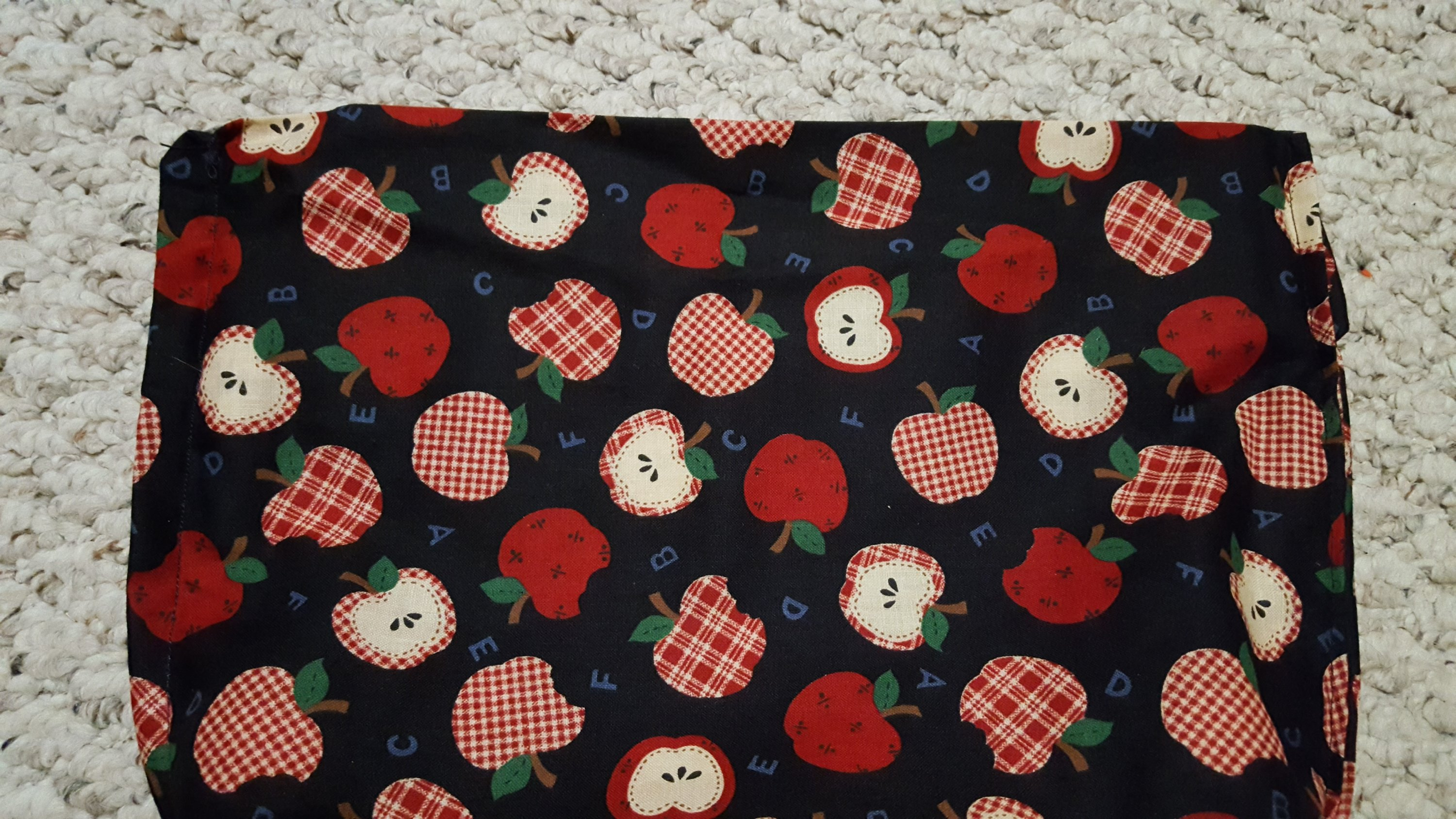 apple fabric layed out to make a microwavable popcorn bag
