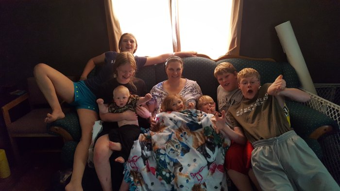 a mom with seven children sitting on a couch large family style