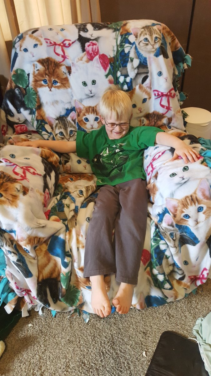 5 year old boy wearing glasses sitting in a rocking chair on a cat blanket