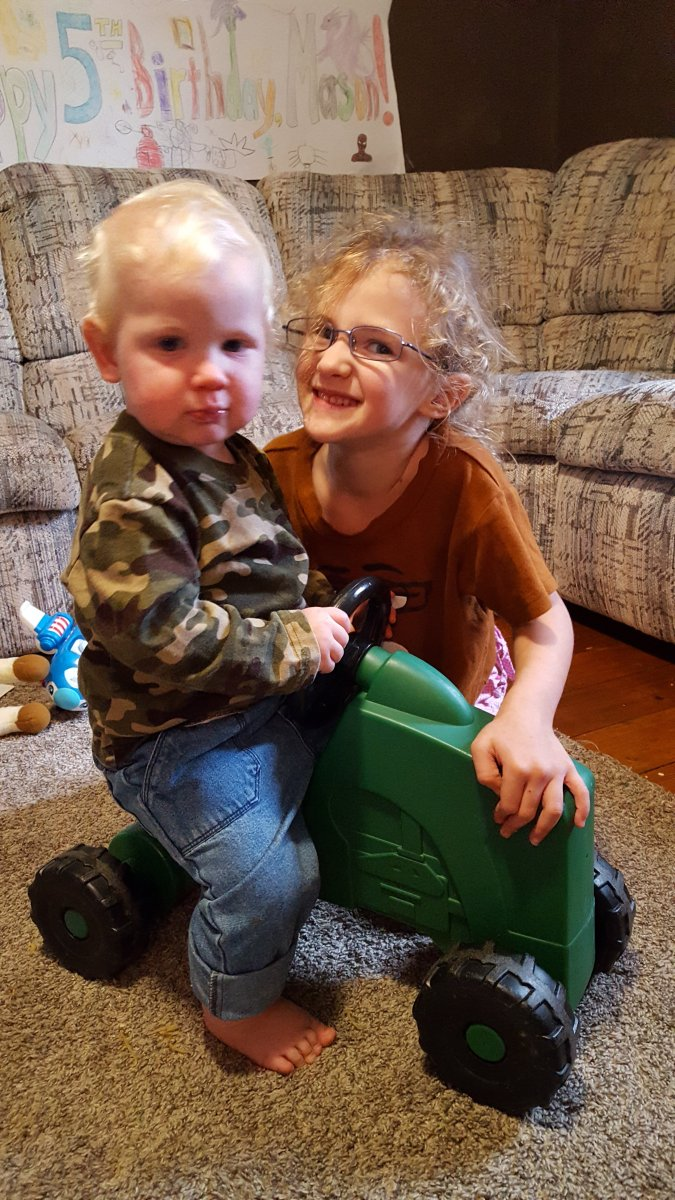 toddler boy riding a toy tractor with 6 year old sister wearing glasses