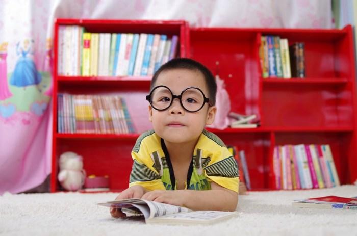 little boy reading glasses books bookshelf child learning child development