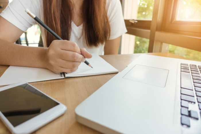 female college student writing pencil and paper laptop desk