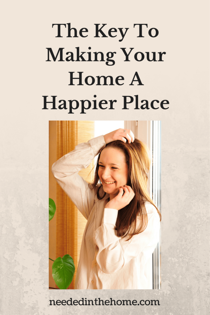 smiling woman in front of window in her home The Key To Making Your Home A Happier Place