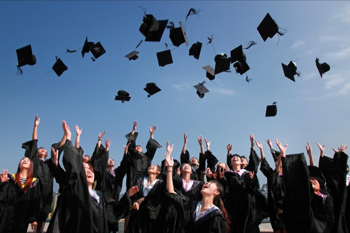 graduates with gowns throwing caps in the air