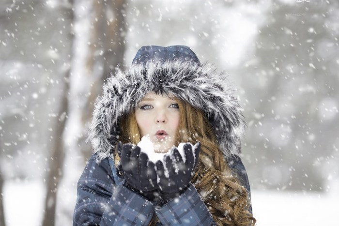 long haired woman in winter coat blowing snow in the air wearing parka and winter gloves top tips for warming your home this winter