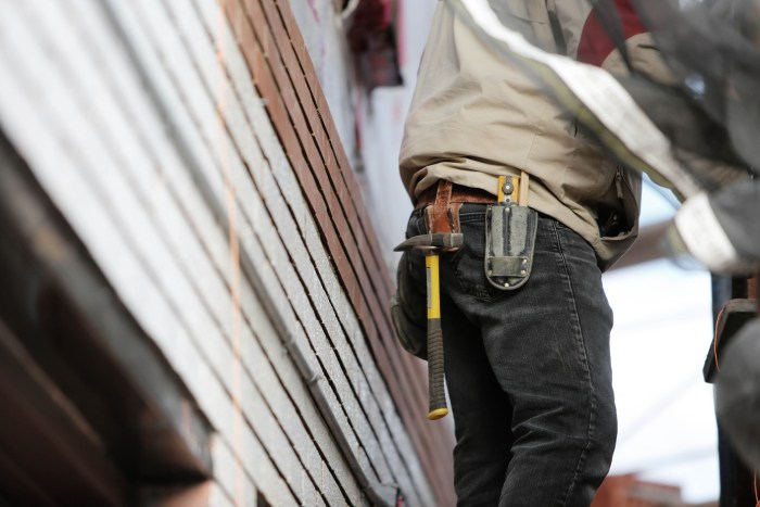 man toolbelt hammer work siding on house Simple Home Improvements That Could Save You Money