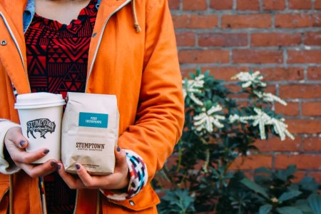 Holding a Stumptown Coffee and bag.