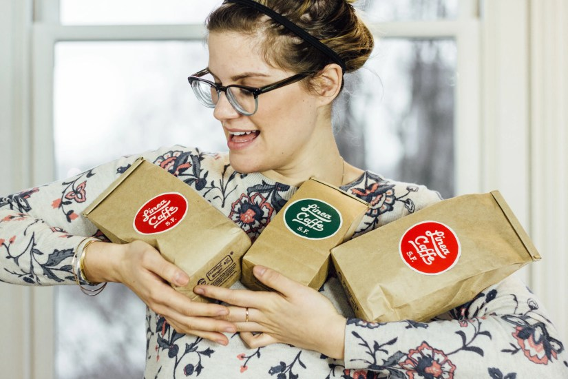Melissa holding a trio of Linea Caffee coffee bags with much love.