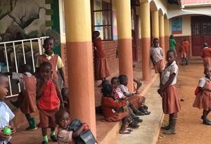 Children sitting in school yard during recess.