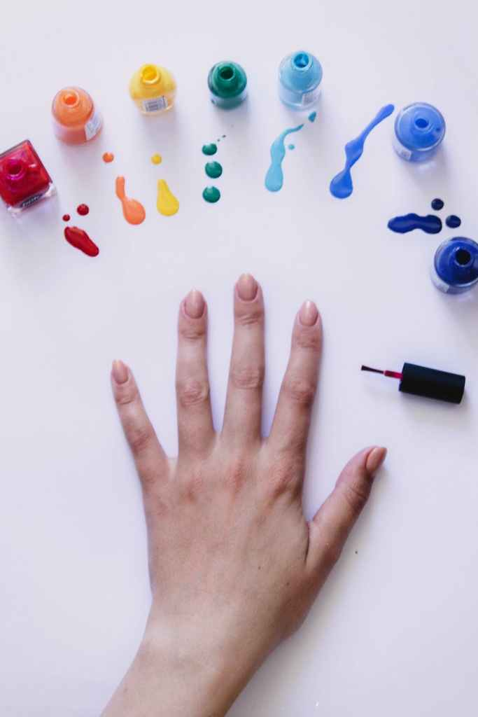crop woman showing manicure with bottles of multicolored nail polishes