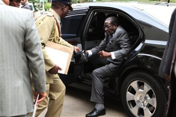 Hold this for me: Mugabe steps out of his armoured Mercedes limousine and hands over a mystery bag to one of his bodyguards.