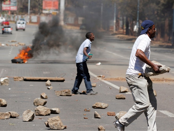 Opponents of Robert Mugabe armed themselves with rocks during the clashes. Credit: Reuters