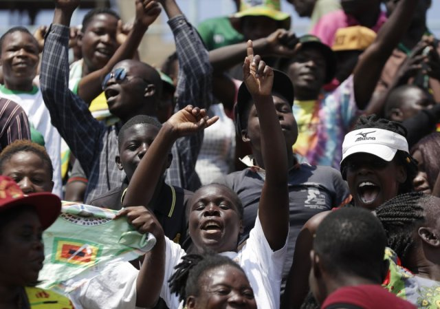 People wait at the Rufaro Stadium in Harare, Thursday, Sept. 12, 2019, where former President Robert Mugabe will lie in state for a public viewing. The body of the former guerrilla leader is to be on view at several historic sites in the next few days but where and when he will be buried has not been announced. (AP Photo/Themba Hadebe)
