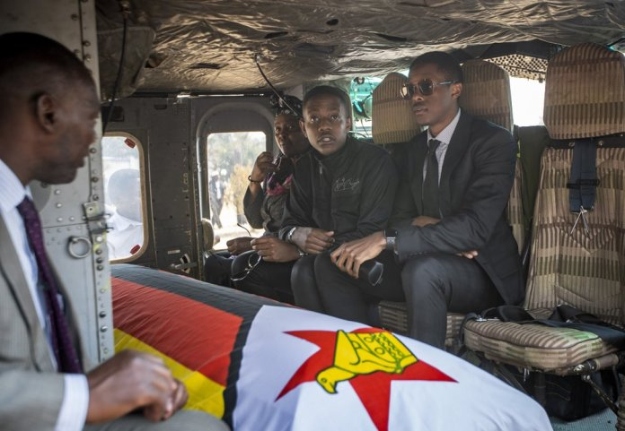 Former president Robert Mugabe's two sons Chatunga Mugabe, center, and Robert Mugabe Junior, right, accompany his casket in an air force helicopter for transport to a stadium where it will lie in state, at his official residence in the capital Harare, Zimbabwe Friday, Sept. 13, 2019. The ongoing uncertainty of the burial of Mugabe, who died last week in Singapore at the age of 95, has eclipsed the elaborate plans for Zimbabweans to pay their respects to the former guerrilla leader at several historic sites. (AP Photo/Ben Curtis)