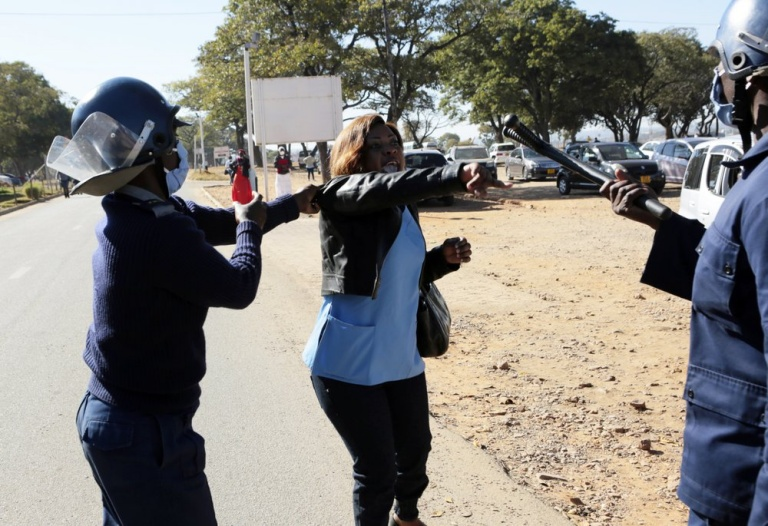 Riot police arrest a nurse who was protesting at a government hospital in Harare, Monday, July, 6, 2020. Thousands of nurses working in public hospitals stopped reporting for work in mid-June, part of frequent work stoppages by health workers who earn less than $50 a month and allege they are forced to work without adequate protective equipment. On Monday, dozens of nurses wearing masks and their white and blue uniforms gathered for protests at some of the country's biggest hospitals in the capital, Harare, and the second-largest city of Bulawayo.(AP Photo/Tsvangirayi Mukwazhi)