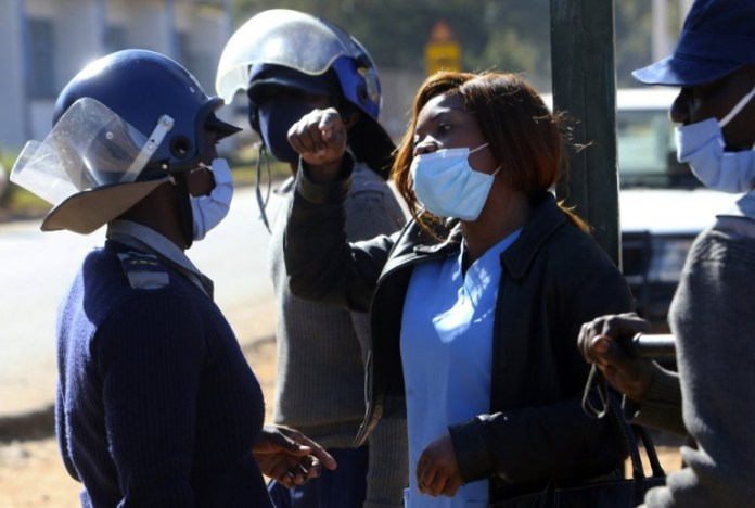 Riot police surround a nurse who was protesting at a government hospital in Harare, Monday, July, 6, 2020. Thousands of nurses working in public hospitals stopped reporting for work in mid-June, part of frequent work stoppages by health workers who earn less than $50 a month and allege they are forced to work without adequate protective equipment. On Monday, dozens of nurses wearing masks and their white and blue uniforms gathered for protests at some of the country's biggest hospitals in the capital, Harare, and the second-largest city of Bulawayo.(AP Photo/Tsvangirayi Mukwazhi)