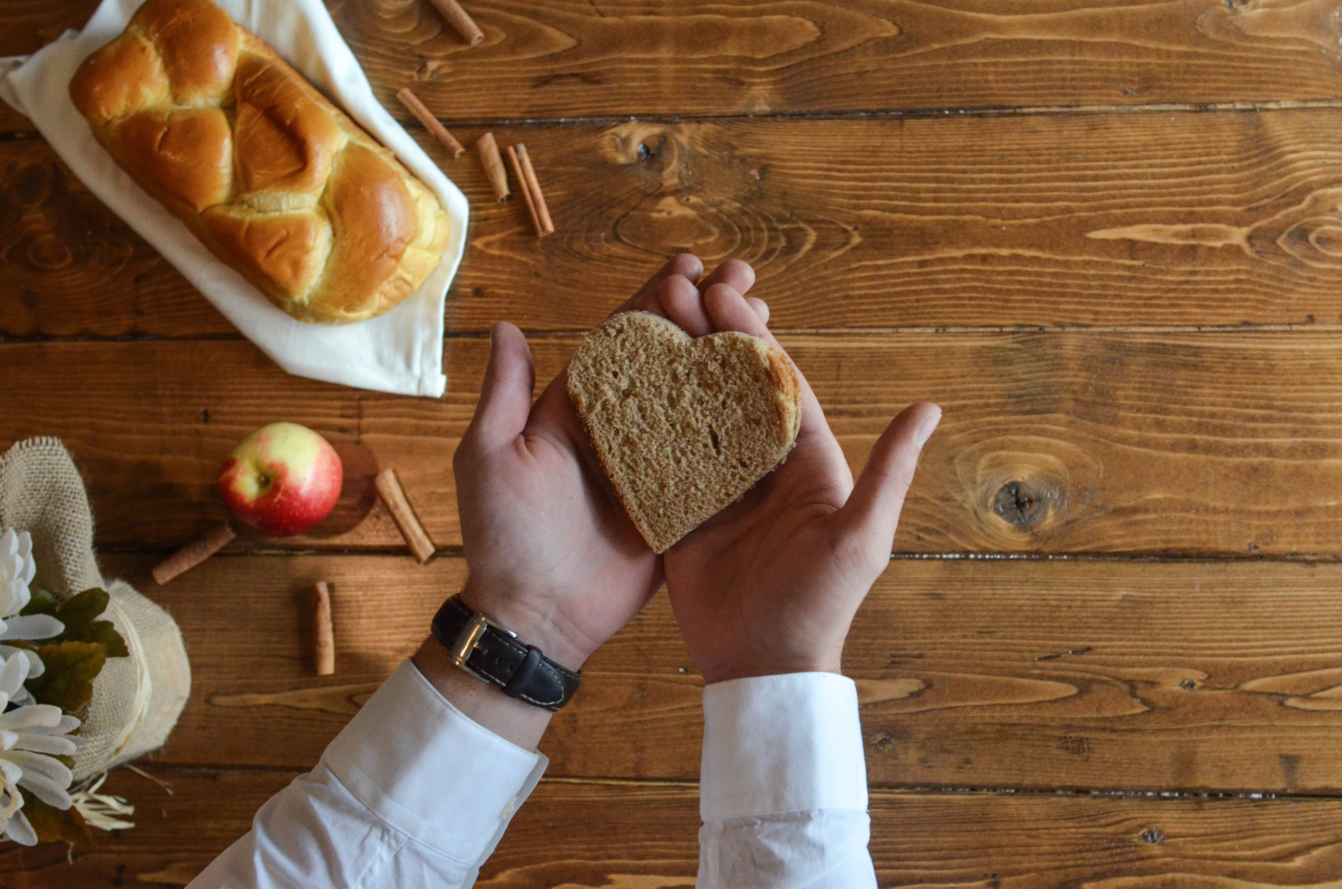 person-holding-heart-shaped-bread-669731