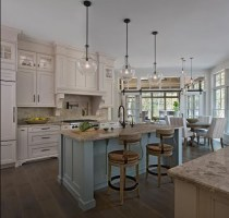 On trend and stunningly white, this kitchen design from Ellwood Interiors, Birmingham, makes the most of natural and hanging light fixtures. Photo by Beth Singer
