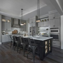 Custom kitchen in colonial model features two-color cabinets and contemporary fixtures lighting the island.