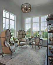 Cozy colonial model sitting room brings in natural light.