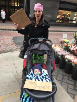 """Maldonian Liz Taegel with baby Max (labelled """"Born Feminist"""") in tow."""
