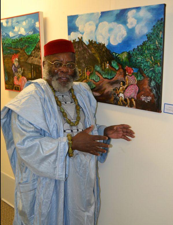 "Artist Efon Elad beside his painting ""Walking the Toddler"""