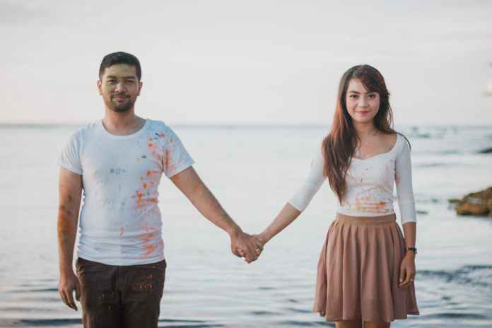 man and woman standing beside body of water