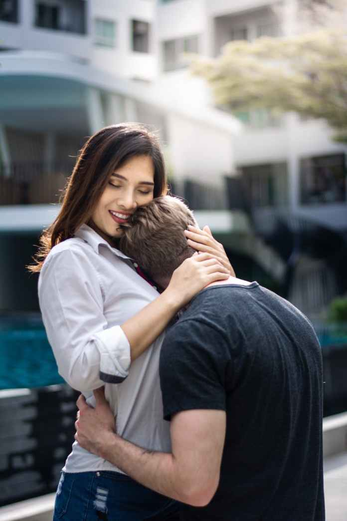 selective focus photography of woman hugging man wearing black t shirt