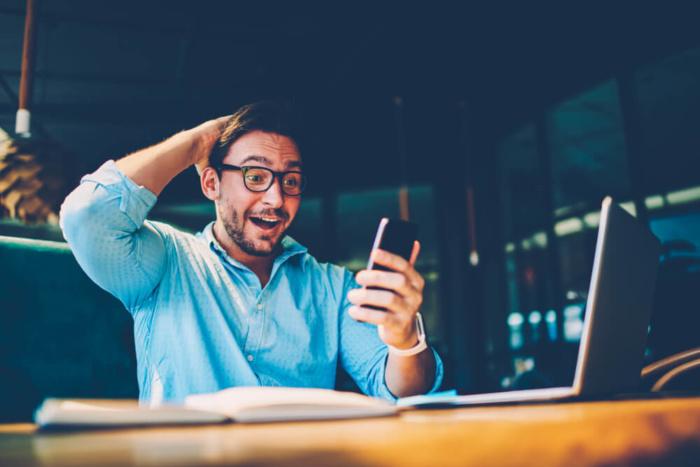 homem impressionado com ganho de dinheiro pelo smartphone dinheiro - homem impressionado com ganho de dinheiro pelo smartphone 700x467 - Como Ganhar Dinheiro na Internet: As 55 Melhores Maneiras (2021)