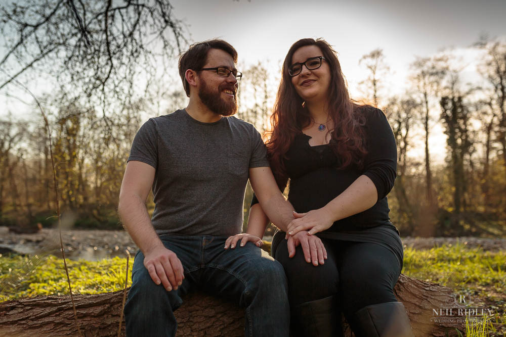 Lancashire Pre Wedding Shoot at Scorton Lake, a young couple hold hands sitting on a log