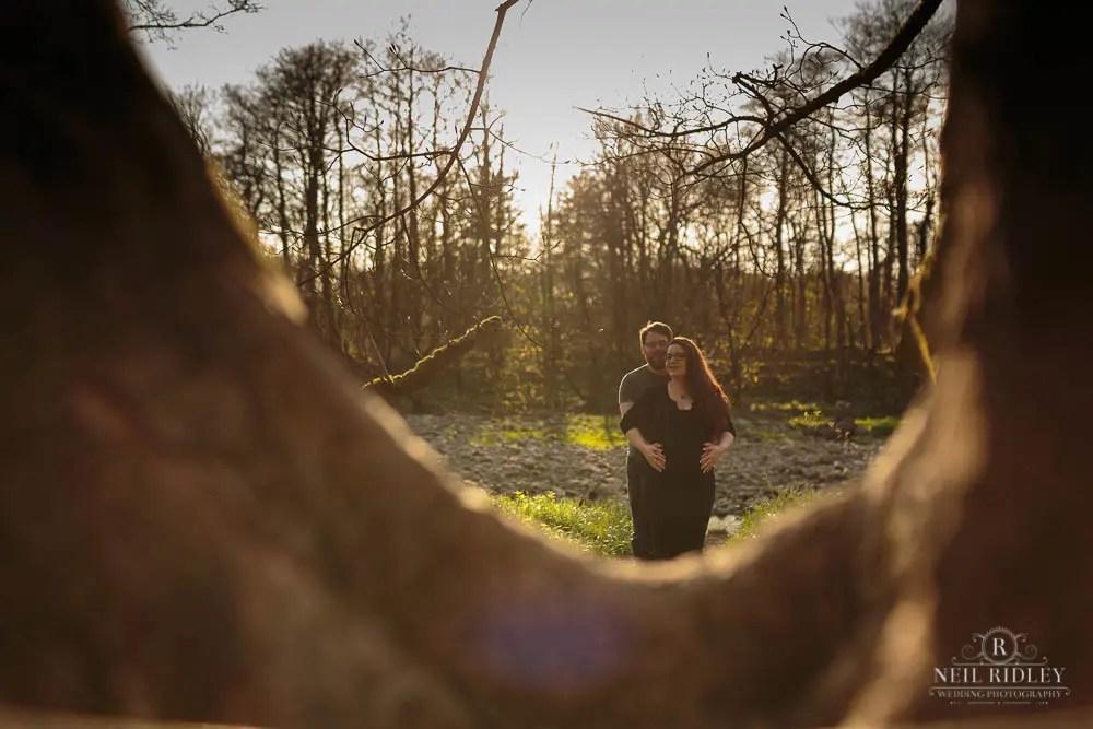 Lancashire Pre Wedding Shoot at Scorton Lake, a young couple viewed through a tree