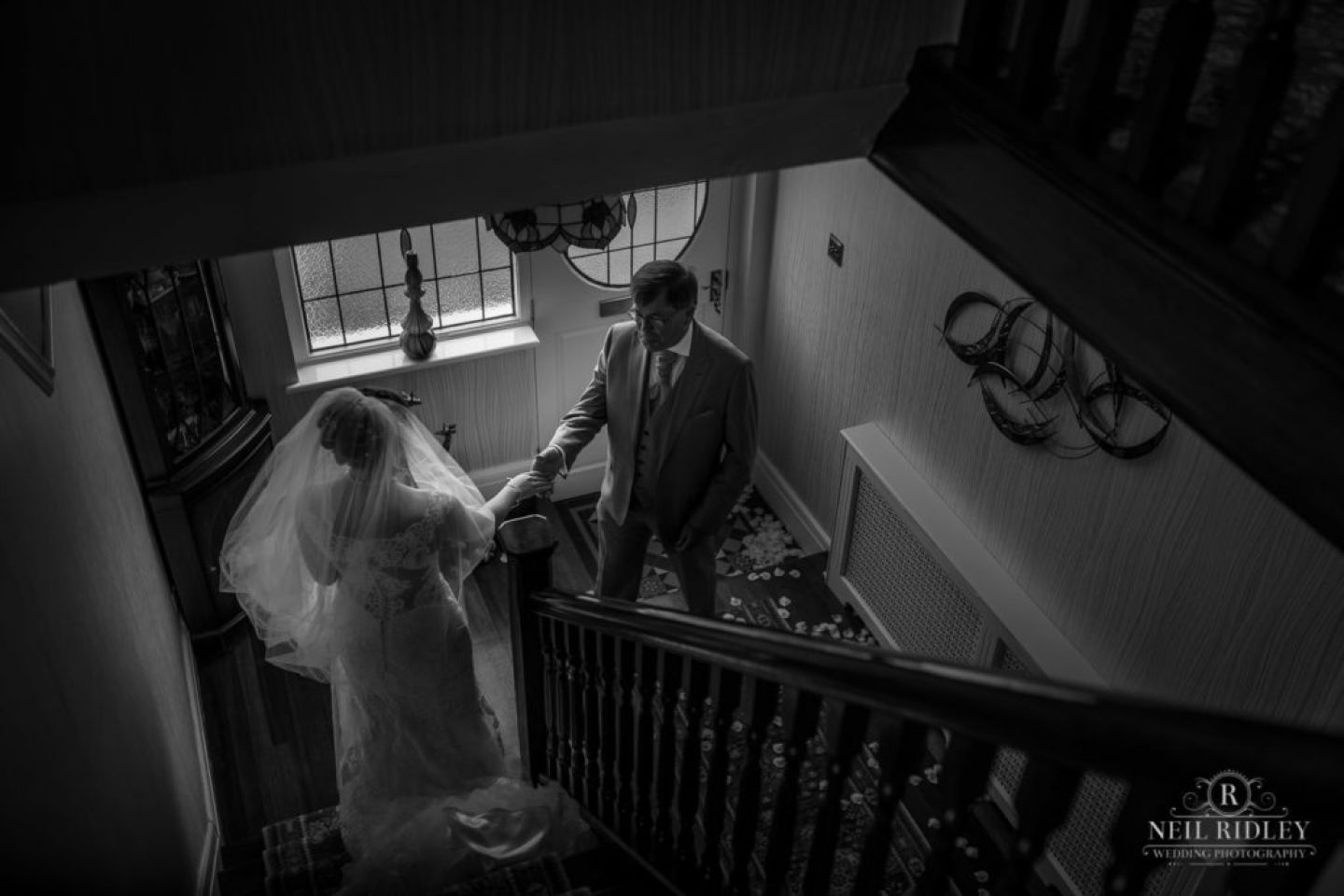 Black and white image of father seeing daughter for the first time in her wedding dress