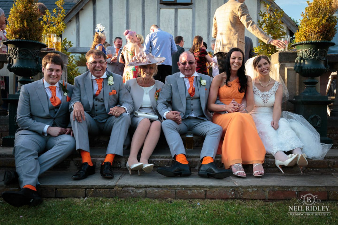 Bride and groom sit with their family in the gardens at The Great Hall at Mains