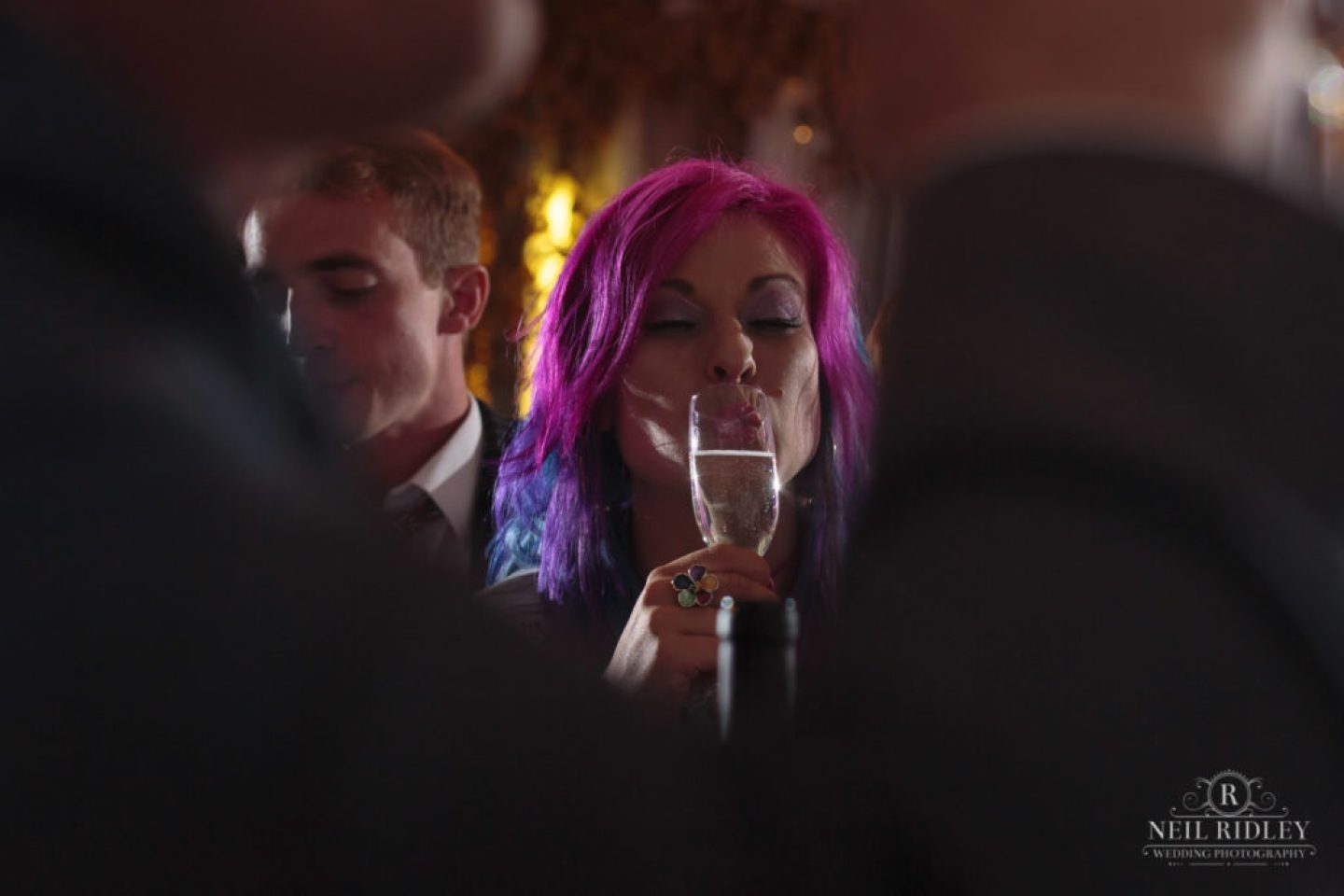 Lancaster Wedding Photographer - Guest with rainbow hair sips champagne at Lancaster Brewery