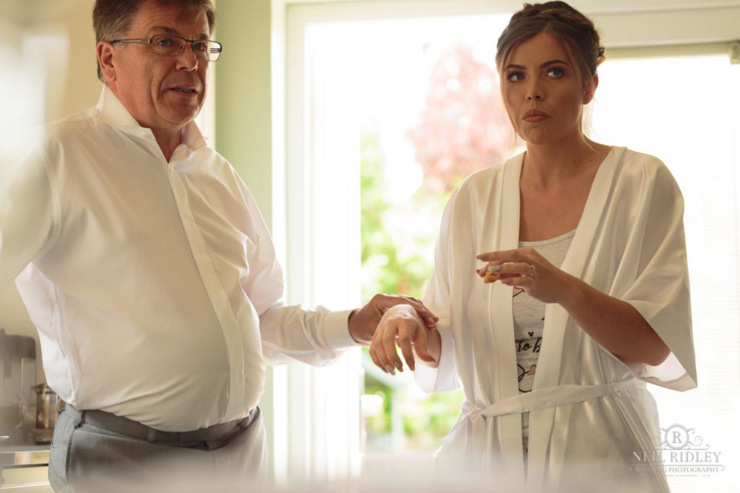 Bride and her father during Bride Prep, brides father is checking Brides pulse