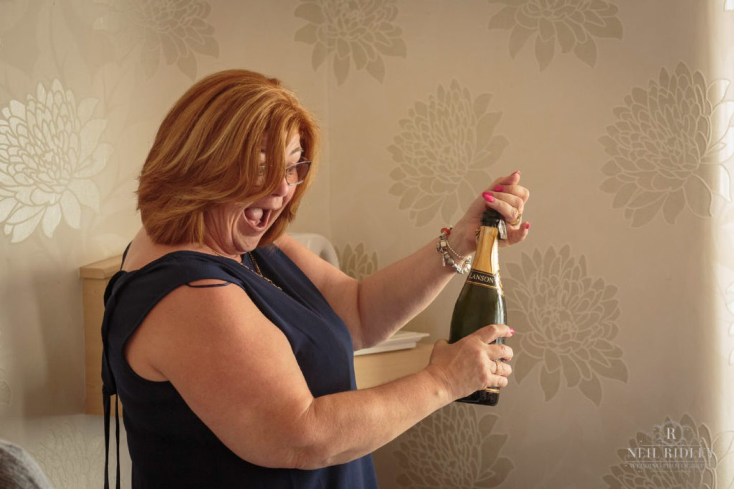 Bridesmaid opening a bottle of champagne during Bride Prep at The Park House Hotel, Blackpool