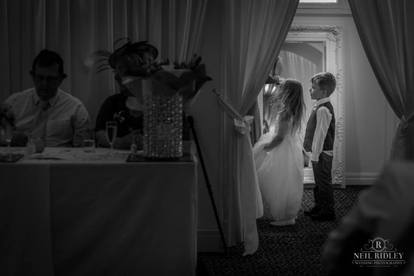 Black and white image of children stood behind the curtain during speeches at The Park House Hotel, Blackpool