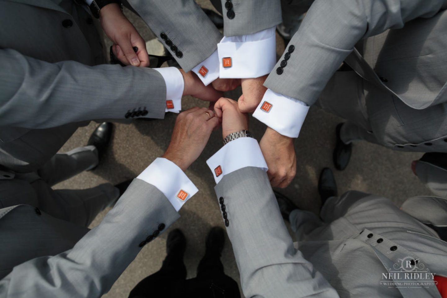Groomsmen all have matching cufflinks with Grey suits