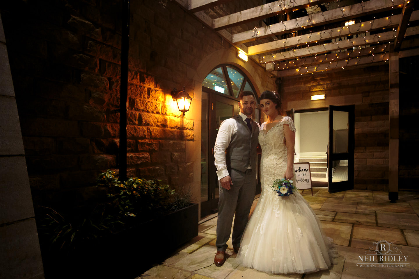 Bride and Groom stand outside with the fairy lights above at The Mill at Conder Green