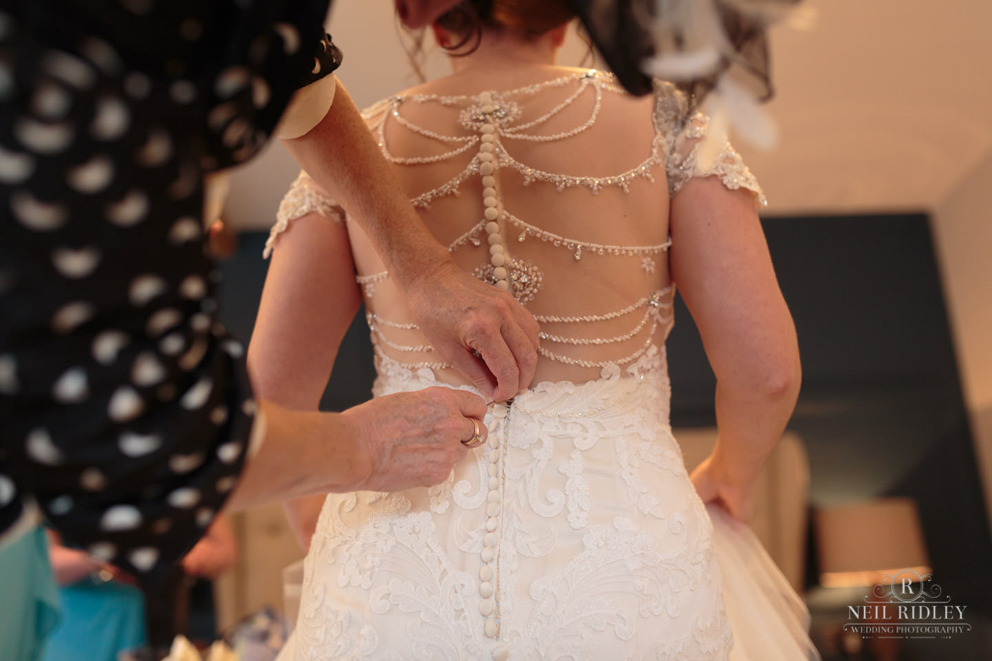 Mother of the Bride fastens the back of the Bride's wedding dress during Bridal Prep at The Mill at Conder Green