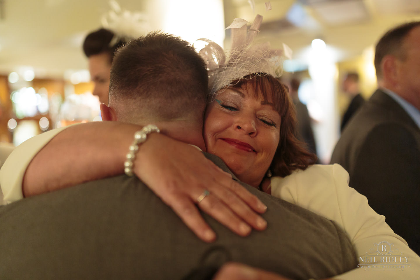 Groom hugs his mom as he waits for his bride at The Mill at Conder Green